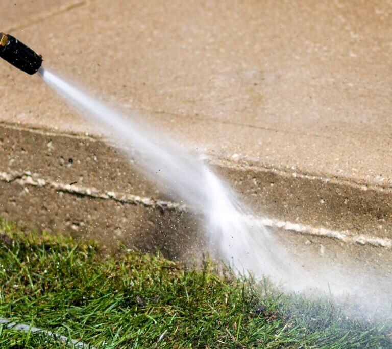 Closeup photo of pressure washer water cleaning the side of a concrete sidewalk